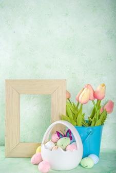 Concetto felice di pasqua con le uova di pasqua nel cestino e fiori primaverili. sfondo di pasqua con copia spazio e cornice per foto