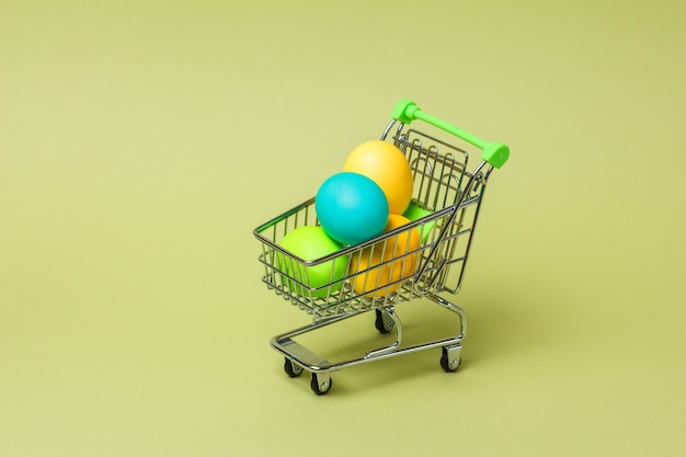 Concetto felice di pasqua con le uova di pasqua nel carrello del supermercato