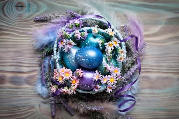 Buona pasqua. congratulazioni sfondo pasquale. uova di pasqua e fiori. sfondo con spazio di copia. messa a fuoco selettiva. vista dall'alto.