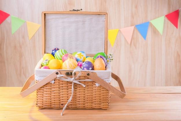 Le uova variopinte felici nel giorno di pasqua nel cestino sul pavimento di legno celebrano le bandiere del partito