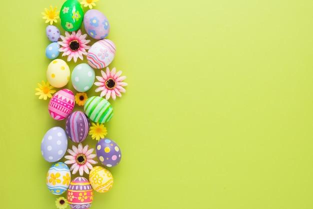 Felice giorno di pasqua uova colorate e decorazioni floreali su carta