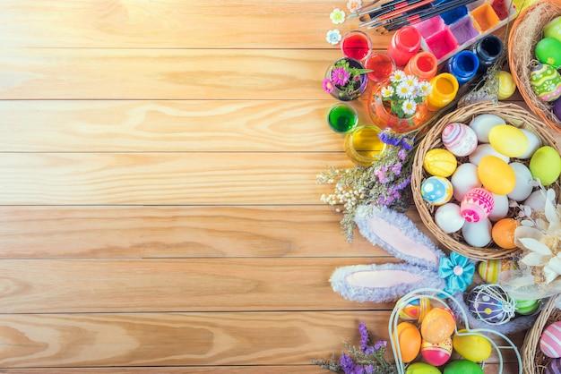 Le uova variopinte felici del giorno di pasqua e fioriscono un insieme di colorante alimentare, pennello acrilico per fai da te sul pavimento di legno marrone con lo spazio della copia
