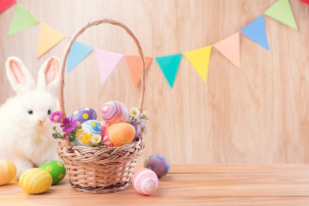 Le uova variopinte ed i fiori del giorno di pasqua felice nel canestro e nel coniglio sul pavimento di legno hanno celebrato le bandiere del partito con lo spazio della copia