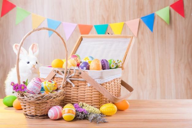 Felice giorno di pasqua uova colorate e fiori nel cestino con coniglio sul pavimento di legno hanno sfocato celebrare le bandiere del partito
