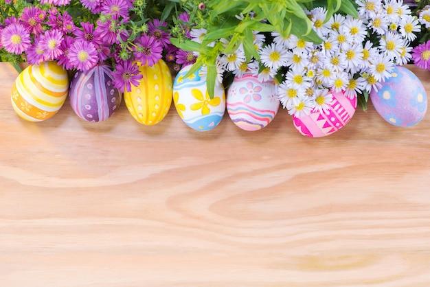 Uova e fiori variopinti felici di giorno di pasqua sul pavimento di legno con lo spazio della copia