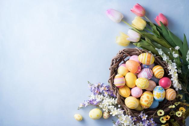 Felice giorno di pasqua uova colorate nel nido e decorazioni floreali su carta