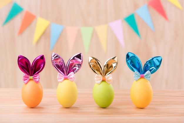 Le uova variopinte felici del giorno di pasqua con le orecchie del coniglietto sul pavimento di legno vago celebrano le bandiere del partito con lo spazio della copia