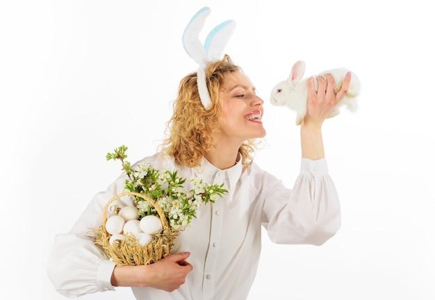 Felice giorno di pasqua, ragazza sorridente in orecchie da coniglio con uova di cesto e coniglio di pasqua.