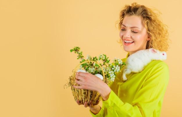 Buona pasqua. donna sorridente con cesto di uova e coniglietto di pasqua.