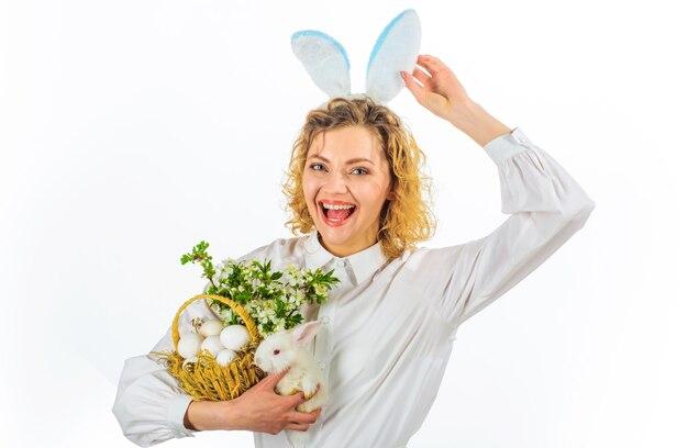 Buona pasqua. donna sorridente con coniglio bianco e cesto con uova.