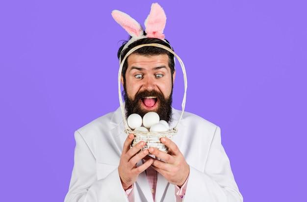 Buona pasqua. uomo barbuto sorpreso con l'uovo del canestro ragazzo nelle orecchie da coniglio. uomo coniglio.
