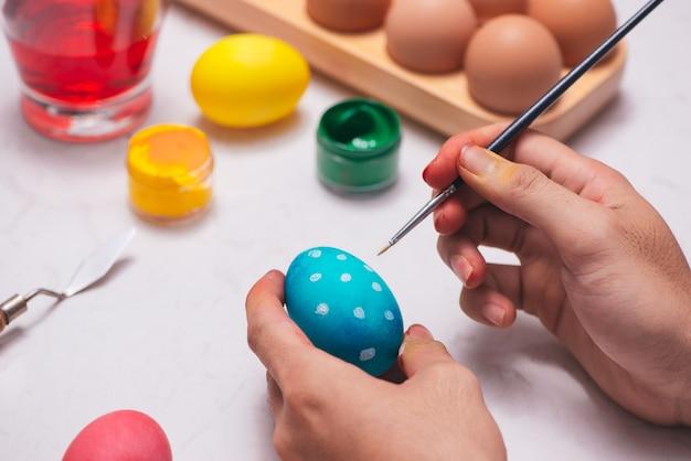 Buona pasqua! padre che dipinge le uova di pasqua sul tavolo.