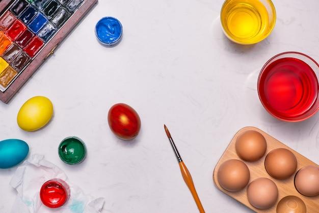 Buona pasqua! amici che dipingono le uova di pasqua sul tavolo.