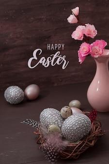 Testo di saluto di pasqua felice con nido e uova su bakcground marrone con fiori rosa sbocciano natura morta chiave bassa
