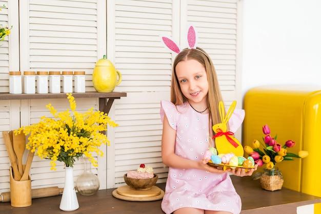 Buona pasqua. un bambino felice si sta preparando per la pasqua. la ragazza tiene un piedistallo a forma di coniglio con uova colorate.
