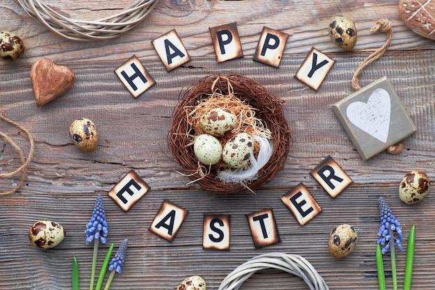 Testo felice dell'iscrizione di pasqua su legno rustico con i fiori della primavera, le uova di pasqua, il cuore di legno e le decorazioni