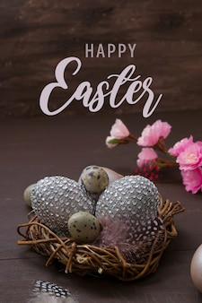Felice pasqua nido con uova su un bakcground marrone con fiori rosa e una confezione regalo. decorazione d'interni decorativa per le vacanze di pasqua