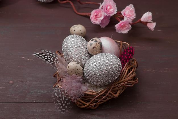 Nido di pasqua felice con le uova su un fondo di legno.