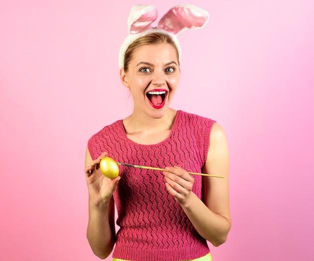 Buona pasqua. uovo sorridente della pittura della donna. la ragazza felice nelle orecchie del coniglietto ha dipinto l'uovo.