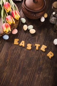 Superficie di pasqua felice, scritte da biscotti, tulipani e uova di quaglia colorate nel cesto di metallo su una superficie di legno