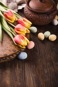 Superficie di pasqua felice con tulipani e uova di quaglia colorate nel cestello di metallo su una superficie di legno. copia spazio