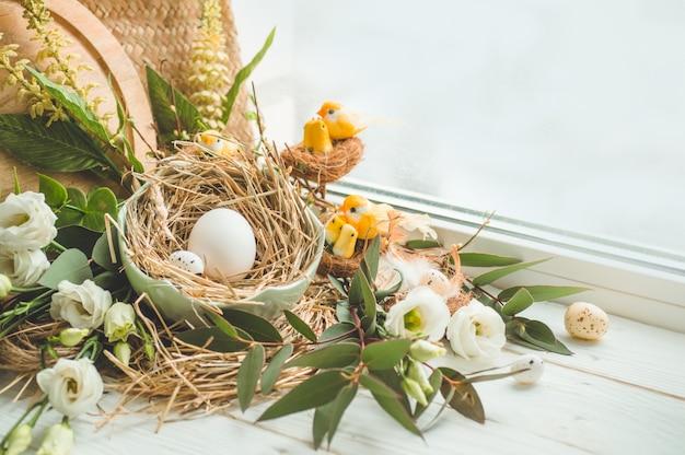 Buona tavola di pasqua. uovo di pasqua in un nido con decorazione floreale vicino alla finestra. uova di quaglia buona pasqua
