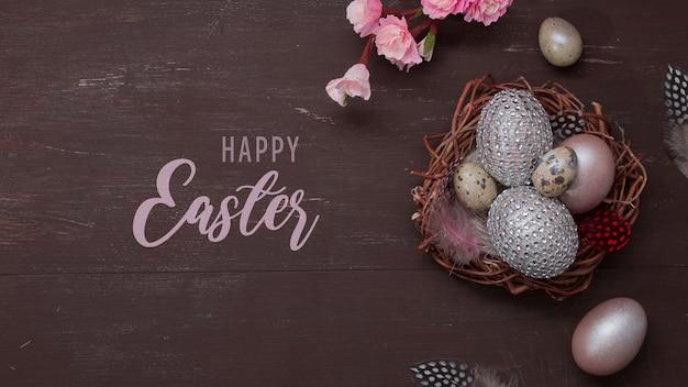 Felice pasqua testo piatto laico nido e uova su bakcground marrone con fiori rosa sbocciano i fiori