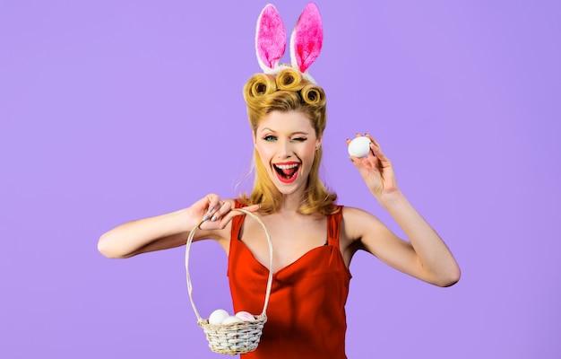 Buona pasqua, donna ammiccante con cesto pasquale, ragazza sorridente con orecchie da coniglio, caccia alle uova.