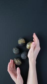 Buona pasqua. mani della donna che tengono le uova di pasqua nere con motivo in oro su sfondo nero. pasqua di lusso