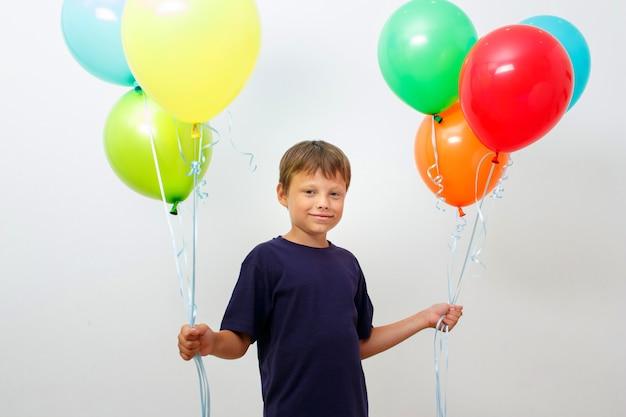 Felice bambino di otto anni con una bracciata di palloncini colorati e luminosi festeggia il compleanno
