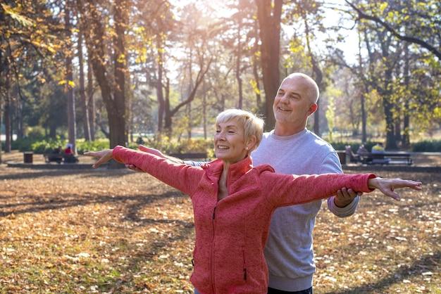 Felice coppia di anziani che si esercita in un parco