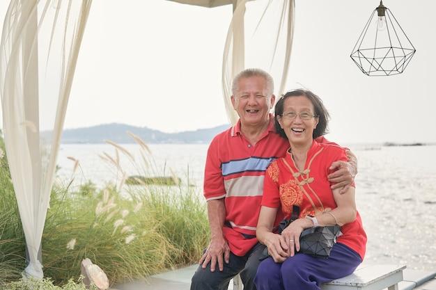 Felice anziana coppia asiatica rilassante in riva al mare in una giornata di sole, felice concetto di pensionamento, viaggio per il concetto di vacanza del capodanno lunare cinese