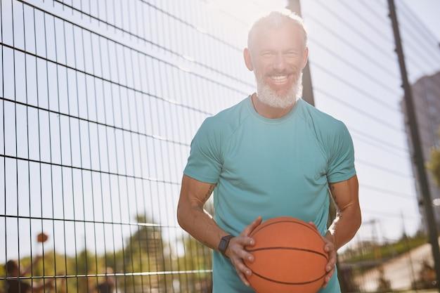 Felice anziano giocatore di basket in abiti sportivi che tiene la palla da basket e sorride alla telecamera mentre