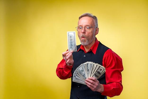 Uomo d'affari anziano felice con fan di banconote da un dollaro