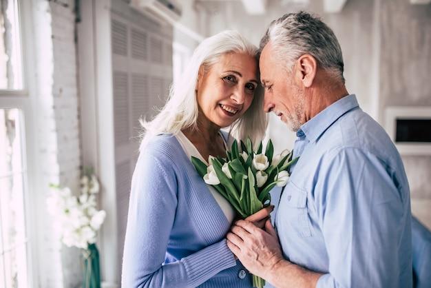 La felice coppia di anziani in piedi con i fiori