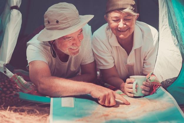 Felice stile di vita anziano con una coppia allegra che pianifica insieme la prossima vacanza di viaggio sulla mappa