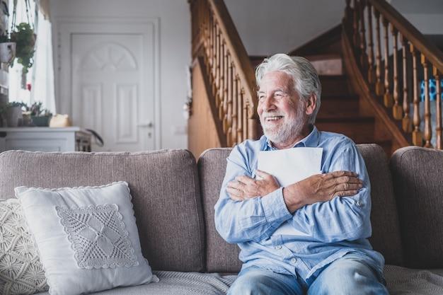 Felice uomo anziano che legge l'accordo di assicurazione sanitaria chiudendo guardando e leggendo i risultati medici. anziano maturo allegro che abbraccia un foglio con i risultati oi risultati. controllo dei test di salute