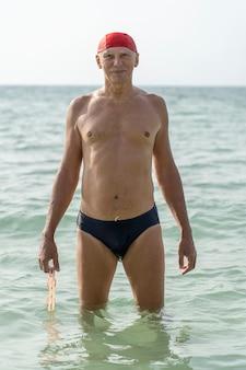 Uomo anziano felice in un cappello da nuoto rosso sulla spiaggia in acqua di mare