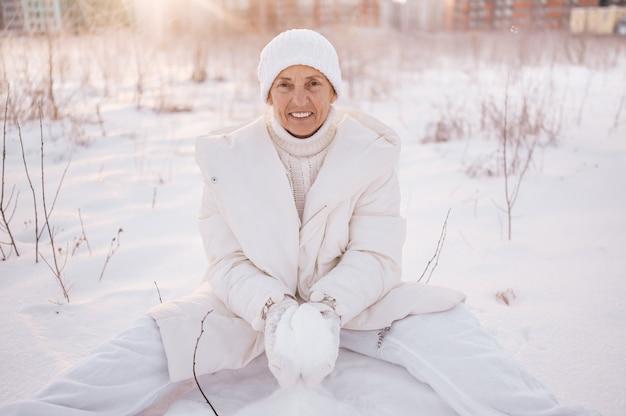 Donna matura senior anziana felice in outwear caldo bianco che gioca con la neve in inverno soleggiato all'aperto.