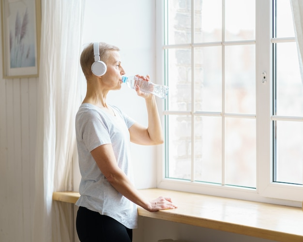Felice donna anziana che beve acqua dalla bottiglia di plastica dopo l'allenamento sportivo
