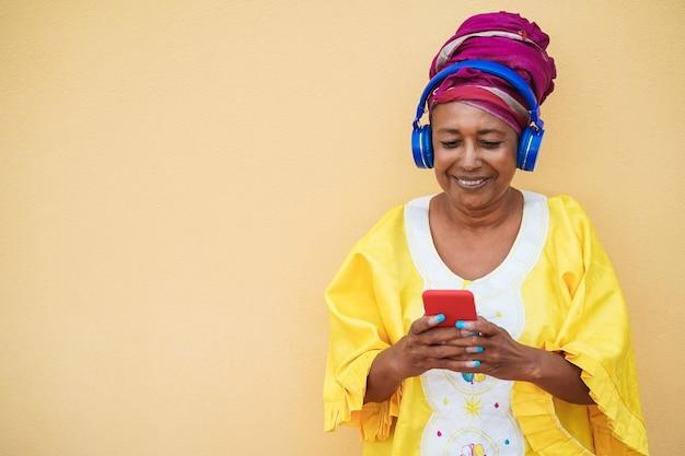 Donna anziana felice che ascolta la musica della playlist sull'app del telefono cellulare