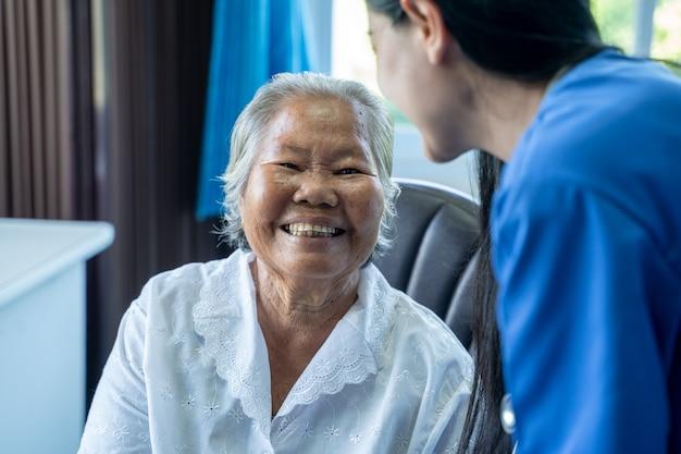 Donna anziana felice, infermiera che dà aiuto psicologico e parla con una donna anziana in una casa di cura.