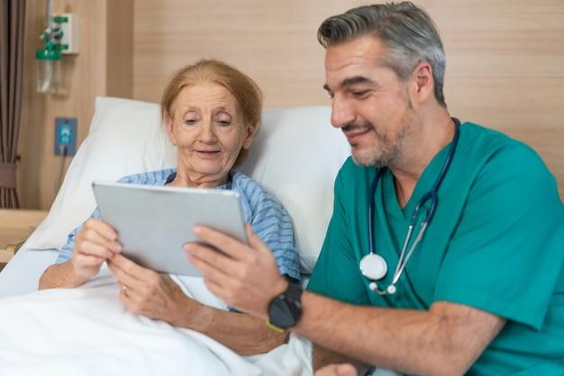 Il paziente anziano felice della donna dopo che il medico dell'uomo maggiore ha spiegato i suoi risultati dell'esame di salute