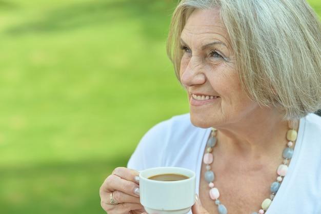 Donna anziana felice con una tazza di caffè
