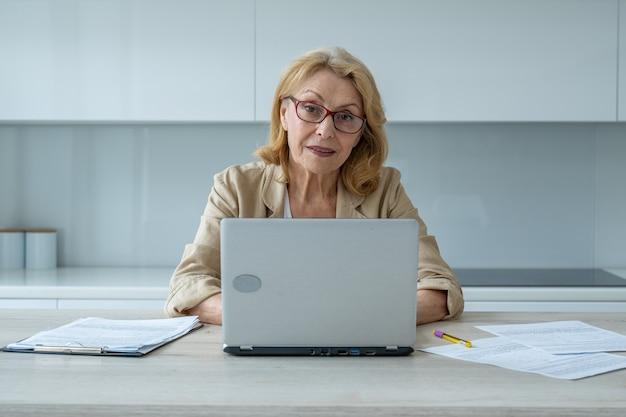 Felice donna anziana con gli occhiali e guardando la telecamera a casa lavora una signora anziana di successo