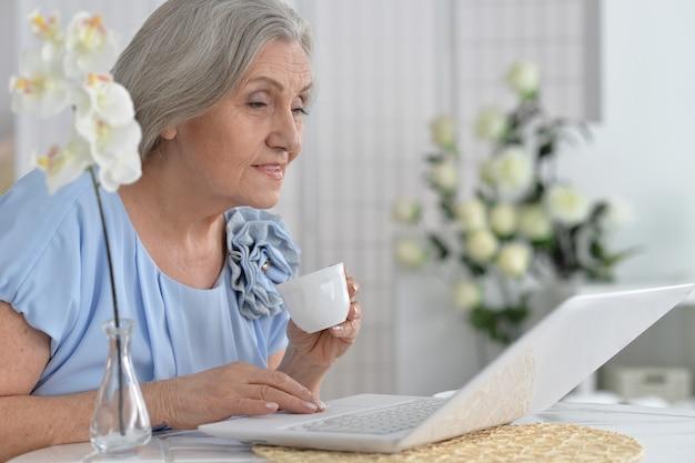 Donna anziana felice con il computer portatile a casa