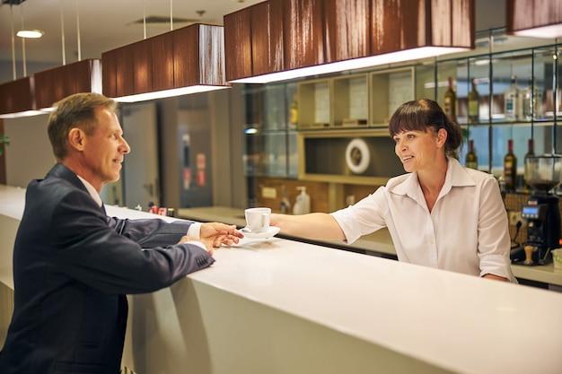 Un uomo elegante e felice sta comunicando con un bel cameriere mentre ordina una tazza di bevanda calda al ristorante