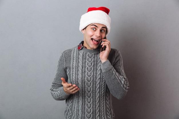 Felice uomo emotivo indossando il cappello di babbo natale parlando per telefono.
