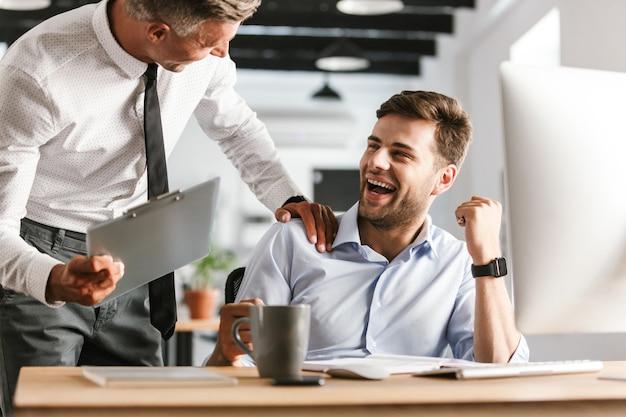 Colleghi di uomini emotivi felici in ufficio a lavorare con il computer.