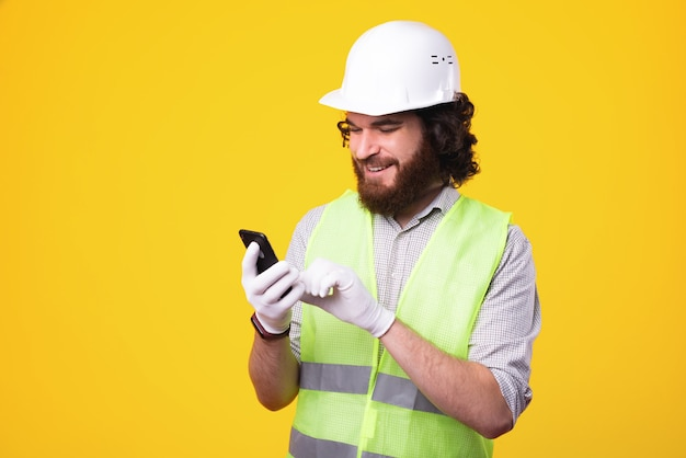 Un ingegnere felice sta mandando un sms a qualcuno attraverso il suo telefono vicino a un muro giallo